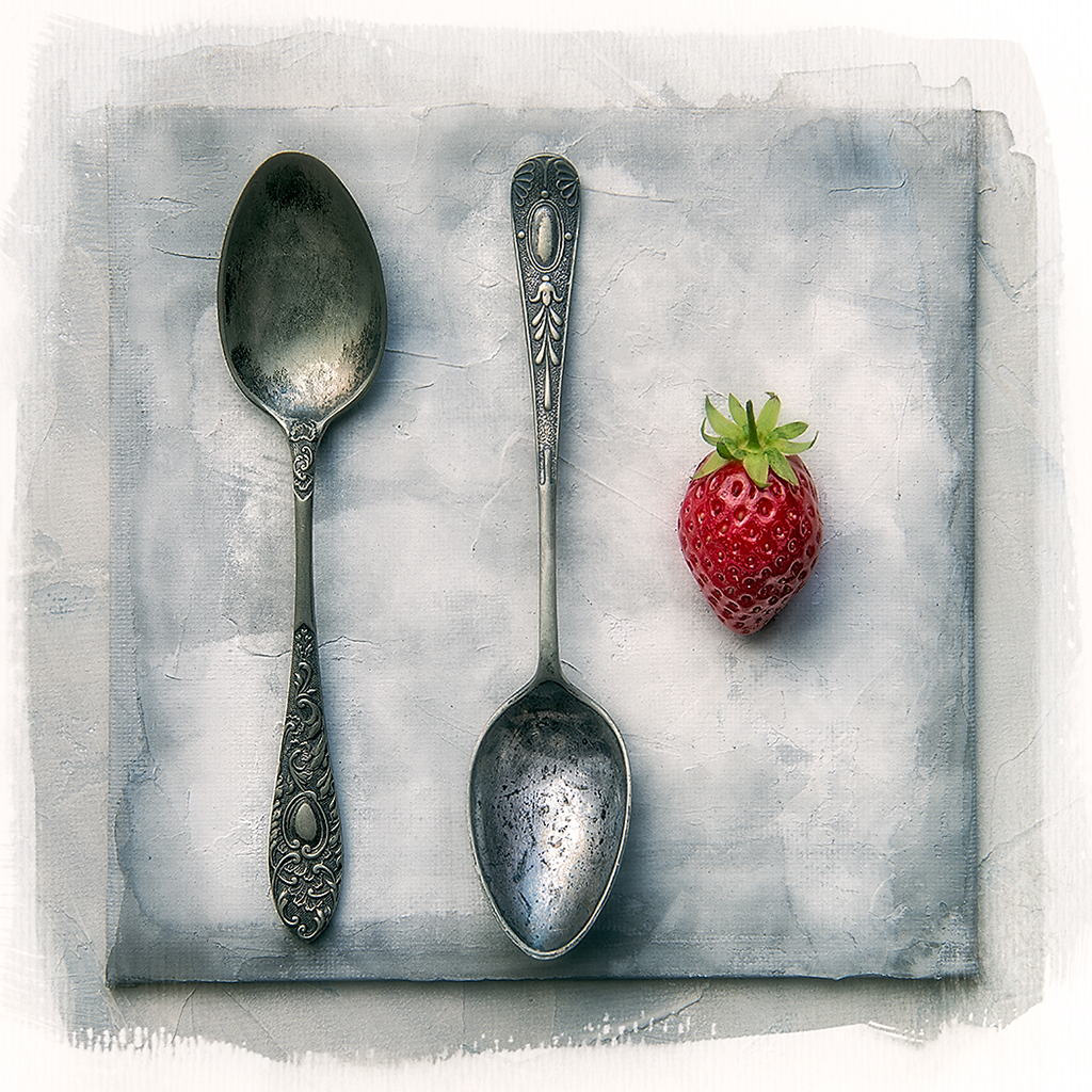 Two spoons and a strawberry